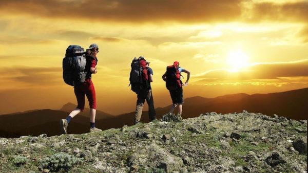 tre fjällvandrare med packning, solnedgång